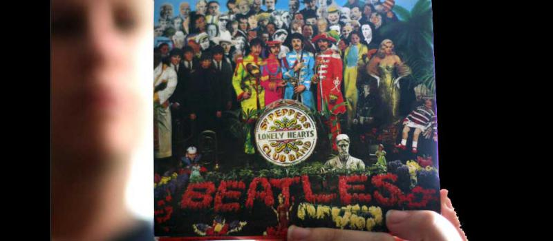 Una mujer sostiene la portada del disco  'Sgt. Peppers Lonely Hearts Club Band'. Foto: AFP